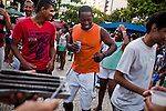 Young men dance and play a mix of samba and funk, during a pre-Carnival celebration in Ipanema, Rio de Janeiro, Brazil, Saturday, Feb. 2, 2013.