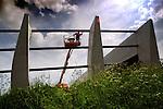 ZWIJNDRECHT -  Langs de snelweg A16 bij Zwijndrecht maakt een medewerker van bouwcombinatie Van Lee/HWVT/VanDrunen de staalconstructie schoon van een nieuw geluidscherm. COPYRIGHT TON BORSBOOM.steekwoorden: Nederland, editorial, bouw, infra infrastructuur bouwnijverheid gww snelweg auto asfalt oranje veiligheid arbo dag, arbo, risico, onveilig valgevaar, hoogtegevaar, rijkswaterstaat, rws, wegwerk, wegwerkzaamheden, reparatie, overlast, verkeer, staand, geluidswal, geluidsisolatie, milieu, isolatie, bescherming, geluidsoverlast, uitzicht