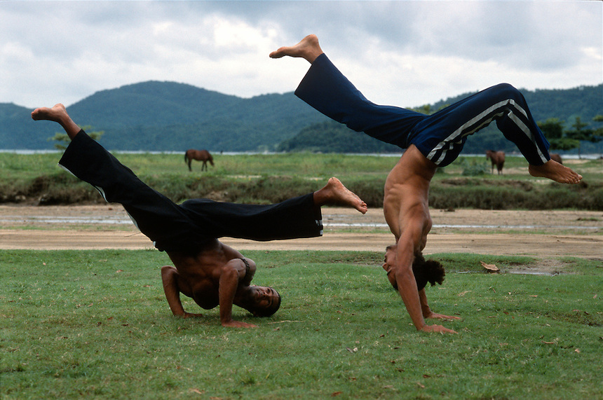 Practicioners of the Brazilian martial art and dance of capoeira practice their moves along the bay in Paratí, Brazil.