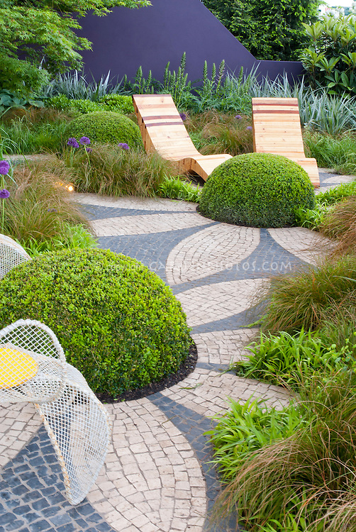 """Fooling the eye in the garden: Rounded shapes and textures in backyard landscape to create Buxus """"flower"""" shrubs. Garden chairs, mosaic deck patio, matching color wall, ornamental onions and grasses, landscaping design, purple and green color combination"""