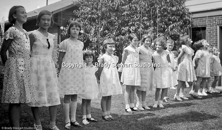Wilkinsburg PA:  View of Sally Stewart's 7th birthday party in the backyard of the Stewart's Wilkinsburg home - 1931.  Girls are playing an old Girl Scout's game of eat the marshmallow.