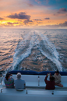 Tourists watching the sunrise while on tour boat, Kauai, Hawaii