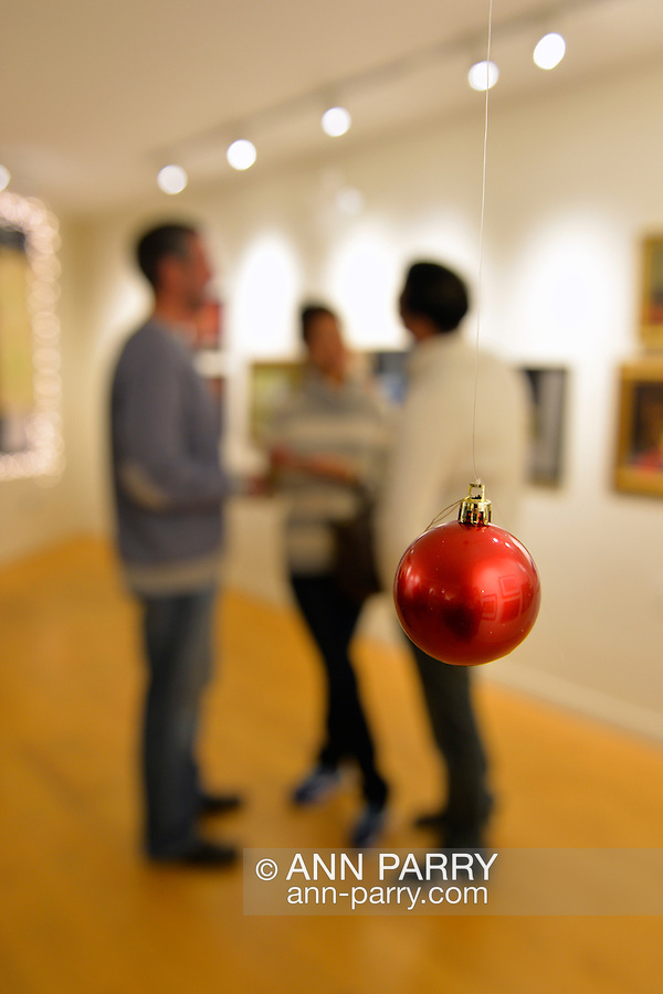 Beyond a red Christmas Ball ornament hanging from the ceiling, a trio of friends talk at the Jingle Boom Holiday Bash, at the festively decorated Main Street Gallery of Huntington Arts Council. Sparkboom, an HAC project, provides events such as this geared to Gen-Y, 18-34 years of age, to address the 'brain drain' of creative young professionals of Long Island. The paintings on the art gallery walls were the Annual Juried Still Life Show.