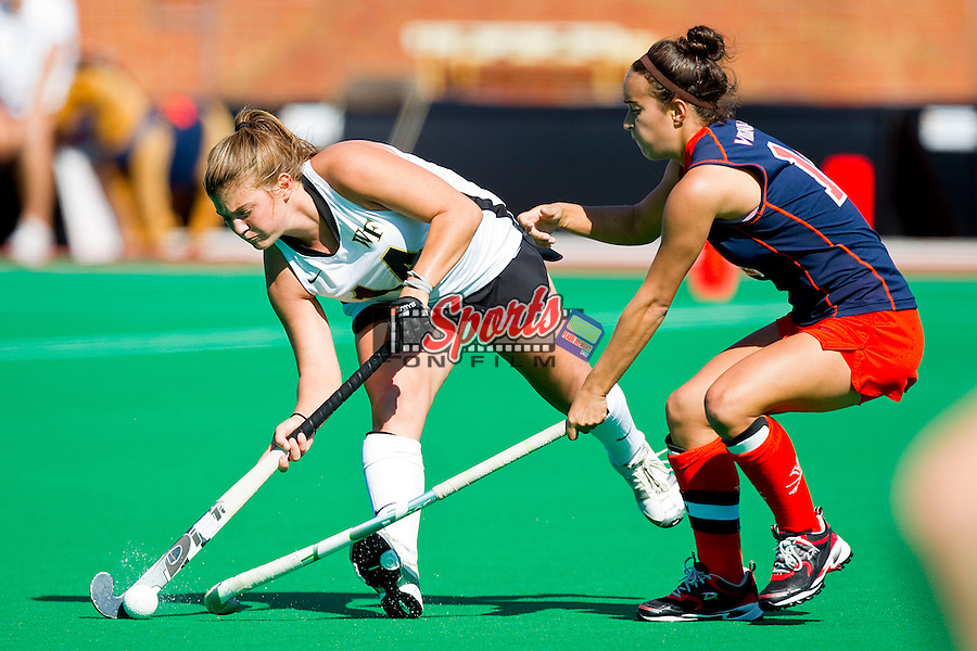 Lauren Greenwald #14 of the Wake Forest Demon Deacons passes the ball away from the defense of Rachel Jennings #14 of the Virginia Cavaliers at Kentner Stadium October 22, 2011, in Winston-Salem, North Carolina.  The Demon Deacons defeated the Cavaliers 5-0..  Photo by Brian Westerholt / Sports On Film