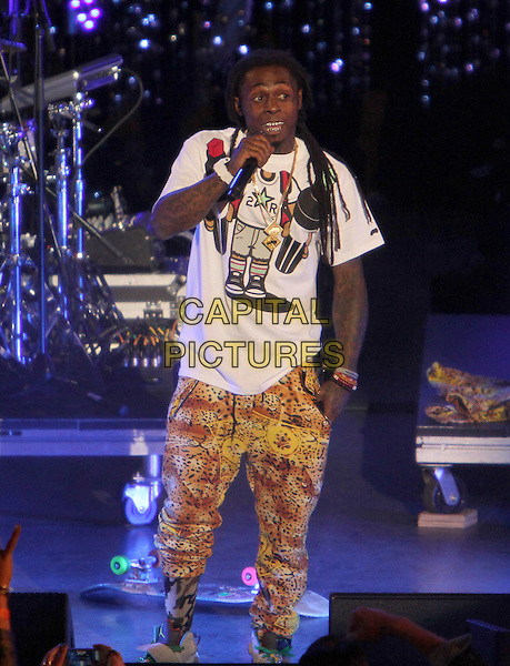 "Lil Wayne (Dwayne Michael Carter, Jr.).Caesars Entertainment Kick-Off Of ""Escape To Total Rewards"" , Los Angeles Show Held At Hollywood & Highland Center, Hollywood, California, USA, 1st March 2012..music concert gig live on stage  full 3/4 length singing  yellow print  microphone  white t-shirt  trainers .CAP/ADM/KB.©Kevan Brooks/AdMedia/Capital Pictures."