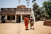 "Shardaben and Kantibhai walk toward their house in Vagpura village,  Anand, Gujarat. ..Shardaben Kantiben, 31; Husband is Kantibhai Motibhai (37).3 children --- 2 girls -  Usha(15) and Lakshmi (18, in pink); 1 boy, Chintan (17).-Kantibhai was already a sperm donor at Dr. Patel's clinic when they came to know about surrogacy and its benefits from Dr. Patel and Shardaben went in for her first surrogacy in early late 2006, early 2007..- Education costs for all three come to Rs. 15,000 per year.- Shardaben was a two-time surrogate. First time she gave birth to twin girls for a Taiwanese couple and the second time a boy for an Indian couple from America (photo on TV set because she's proud that it was a boy).- The second time she became emotional and they got a gold ring of Rs. 1,500 made for the boy, which they presented to the biological parents. They are not in touch with either couple..- From the two surrogacies, they earned a little over 700,000rupees..-200,000rupees will be given as dowry for Lakshmi's wedding..- They leased agricultural land (Rs. 2 lakhs for five years) which earns them Rs. 60,000-70,000 a year; they bought two buffaloes worth Rs. 60,000 and make almost 6000-7000 per month selling milk; they bought a motorbike for Rs. 25,000; they put some money into house repairs and the construction of toilets, and opened a fixed deposit in Shardaben's name for Rs. 1.5 lakh and one in the name of their son, Chintan, for Rs. 25,000..Quotes..""Everyone says they'll keep in touch and take down addresses and phone numbers but nobody looks back. And I guess it works well. Our main interest was in the money. Their main interest is in the baby."" - KantiBhai.""Their rules apply at the surrogate house. It does curtail the freedom. When I used to go, everybody would just be lying. They count the days when they can go back."" - Kantibhai.""Ours is natural birth but surrogacy is a man-made pregnancy. There's a lot of risk. She must have taken at least 300 injections."" - Kantibh"