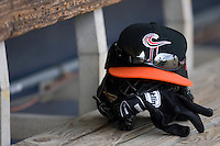 A Norfolk Tides cap sits on top of a glove and batting gloves in the home dugout at Harbor Park June 7, 2009 in Norfolk, Virginia. (Photo by Brian Westerholt / Four Seam Images)