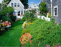 Cape Cod National Seashore, MA <br /> Flower garden with weathered cottage on Provincetown's Commercial Street
