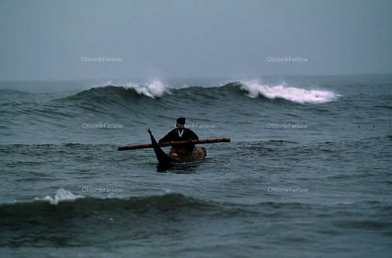 "A young boy paddles a tortora reed boat that fishermen use in the little village north of Lima.  The caballitos, or ""little horses,"" are the traditional for fishermen in the region."