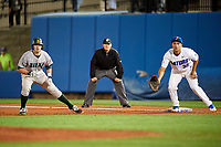 Siena Saints Jordan Bishop (4) leads off first base as Keenan Bell (32) holds him on with umpire Chris Tipton looking on during a game against the Florida Gators on February 16, 2018 at Alfred A. McKethan Stadium in Gainesville, Florida.  Florida defeated Siena 7-1.  (Mike Janes/Four Seam Images)