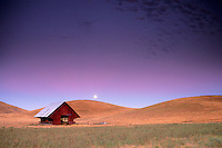 Full moon rising in purple evening sky light over golden grass hills, field, and barn, near Livermore, California.