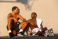 Two friends enjoy talking after a pickup game of basketball.