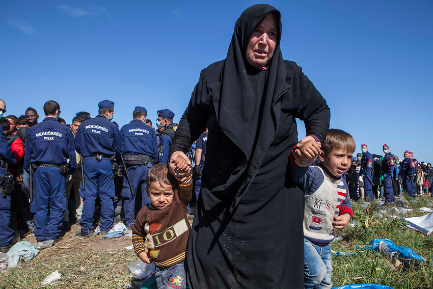 Refugees, mostly Syrian are prevented from moving further towards the interior of Hungary and are kept surrounded by Hungarian police. Refugees were slowly loaded on buses to be transported to a nearby refugee camp or processing center.. Refugees at Roszke Crossing on Serbian-Hungarian Border.