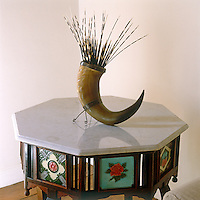 An arrangement of porcupine quills in an antique drinking horn has been placed on a marble-topped table inlaid with brightly glazed ceramic tiles
