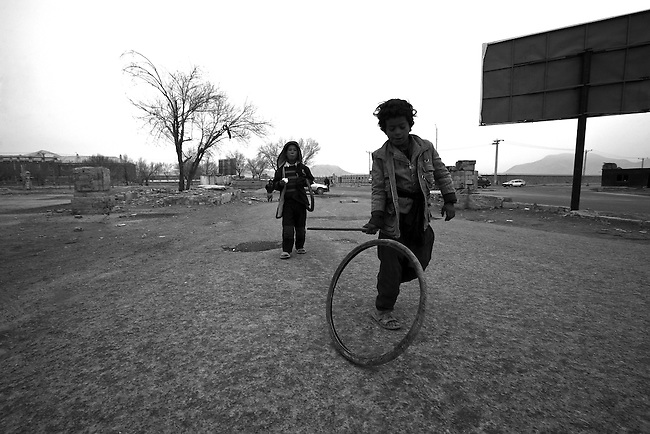 A boy plays with a bicycle tire near  the ruins of the Darul Aman palace on the  outskirts of Kabul, Afghanistan. Feb. 2, 2009.