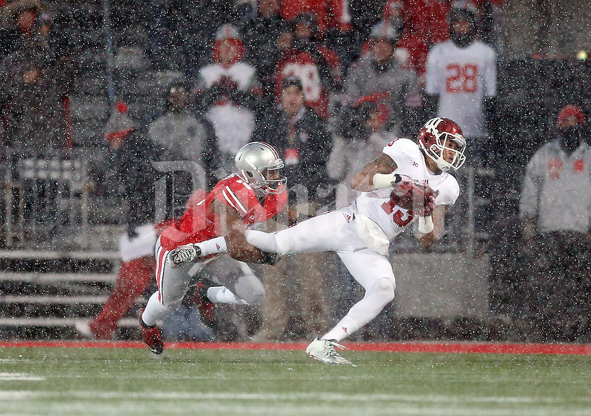 Ohio State Buckeyes defensive back Cam Burrows (16) makes a tackle on Indiana Hoosiers wide receiver Kofi Hughes (13) during the third quarter of their college football game at Ohio Stadium in Columbus, Ohio on November 23, 2013.  (Dispatch photo by Kyle Robertson)