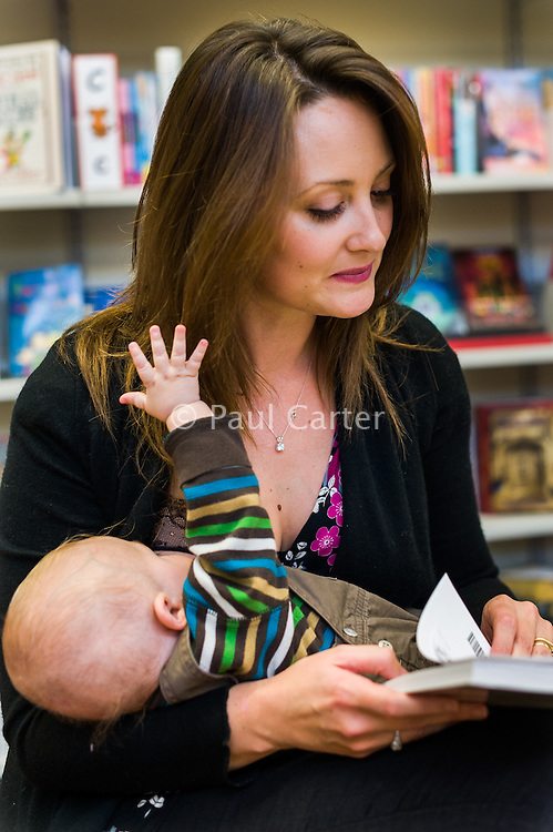 While reading a book a young woman breastfeeds her baby in a library.<br /> <br /> 11 November 2011<br /> Hampshire, England, UK