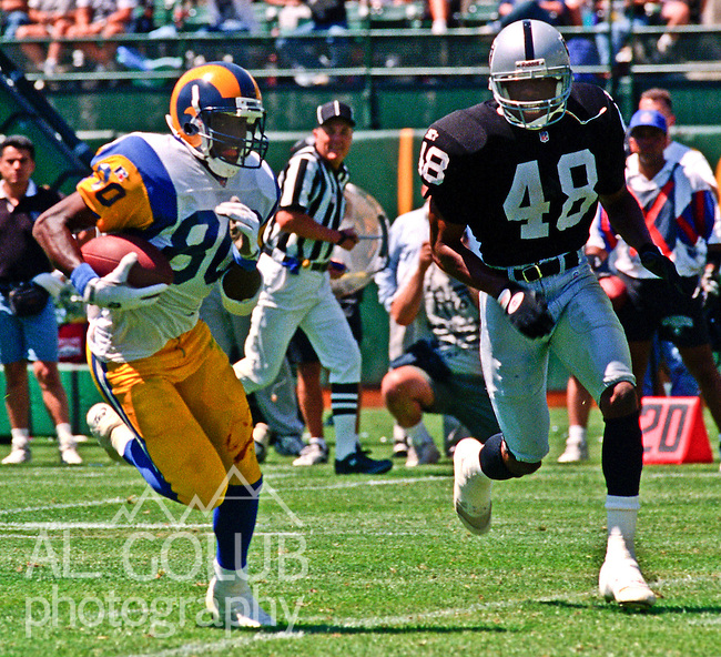 Oakland Raiders vs. St. Louis Rams at Oakland Alameda County Coliseum Saturday, August 12, 1995.  Raiders beat Rams  27-22.  Oakland Raiders defensive back Najee Mustaffa (48) moves in on St. Louis Rams wide receiver Isaac Bruce (80).
