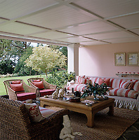 This outdoor living room is furnished with a large comfortable sofa and a selection of wicker armchairs