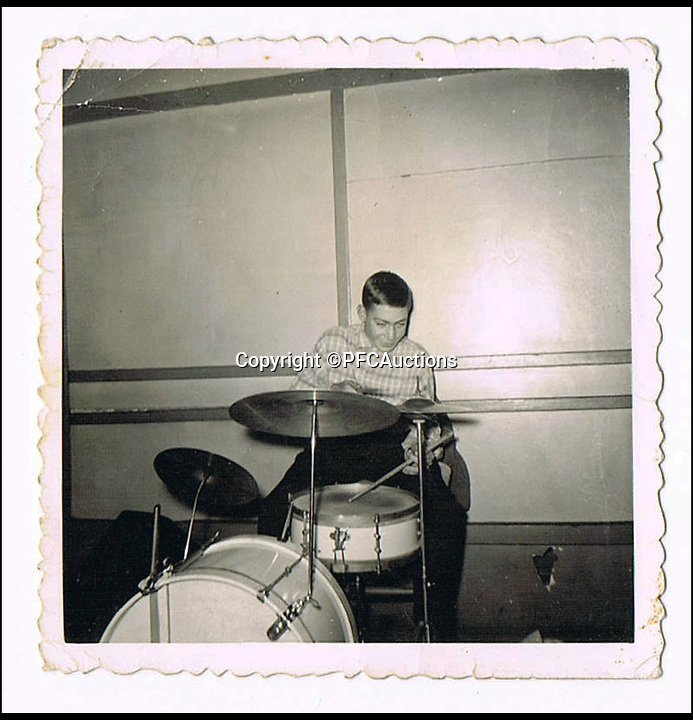 BNPS.co.uk (01202 558833)<br /> Pic: PFCAuctions/BNPS<br /> <br /> ***Please Use Full Byline***<br /> <br /> A young Charlie Watts playing the drums. <br /> <br /> Grainy snaps of Rolling Stones drummer Charlie Watts' first ever performance aged 12 have come to light 50 years after the legendary group shot to fame.<br /> <br /> The black and white photographs show Watts sat at a drum kit at St Andrew's Church Hall in nearby Kingsbury in north west London in 1954 performing with his first band which he formed while still a schoolboy.<br /> <br /> The young Watts had emulated revered jazz drummer Buddy Rich by painting his initials on the front of the bass drum.<br /> <br /> The two 2.5-inch square photos were taken by Nick Rayner, a former neighbour of Watts' in the Wembley area of London he grew up in.<br /> <br /> They are tipped to fetch 5,000 pounds when they are sold by Bristol auction house PFC Auctions.