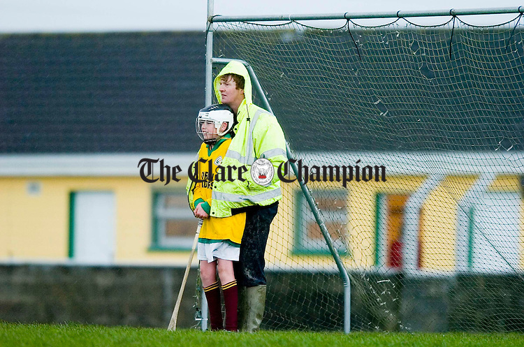 Umpire Thomas Griffin provides shelter to Clonbony goalie ???? Rynne during a shower in the U-14 West Clare Hurling final  against Kilrush at Kilmihil. Photograph by John Kelly.