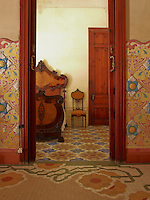 Floral motifs on the tiled floor of this small bedroom echo a more exotic pattern depicted on the wall by local artist Hippolyte Montseny