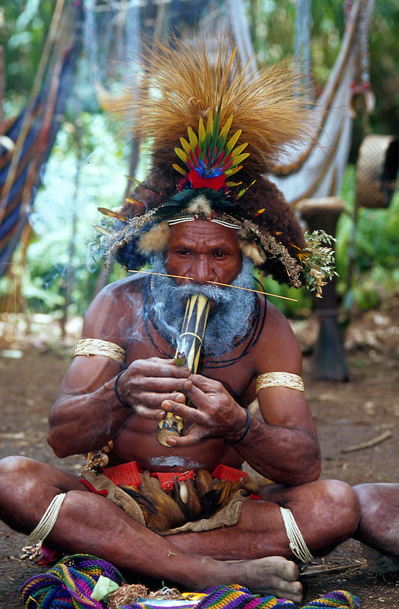 Portrait of a Huli Wigman-warrior; he has an ornate headdress, face paint and smokes a pipe. Papua New Guinea.