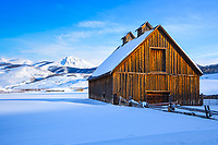 An old barn near Brush Creek in  Crested Butte, Colorado greets the morning sun on a cold winter day.