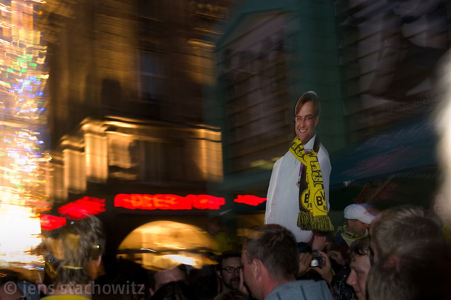 On the ancient marketplace in Dortmund fans celebrate a party because of the title win of their favorite soccer club BVB 09 in the German Premium League. Here they display the cardboard cut-out of Juergen Klopp, the trainer of the BVB 09.