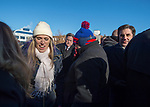 Mineola, New York, USA. January 1, 2018. At left in white cap, SUE MOLLER makes her way through crowd after historic swearing-In of LAURA CURRAN as Nassau County Executive. Town of North Hempstead Town Clerk WAYNE WINK is at far right. Temperature was a freezing 14 ℉ Fahrenheit / -10 ℃  Celsius for the outdoor ceremony held in front of Theodore Roosevelt Executive & Legislative Building, and people in audience stood close together on and near the vast entrance stairs steps.