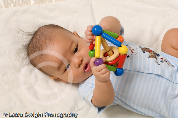 4 month old baby boy Chinese American on back or side grasping toy looking at it horizontal