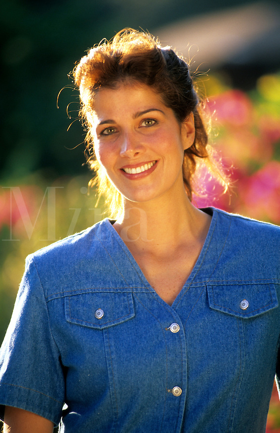Portrait of hispanic woman smiling with flower garden in the background.