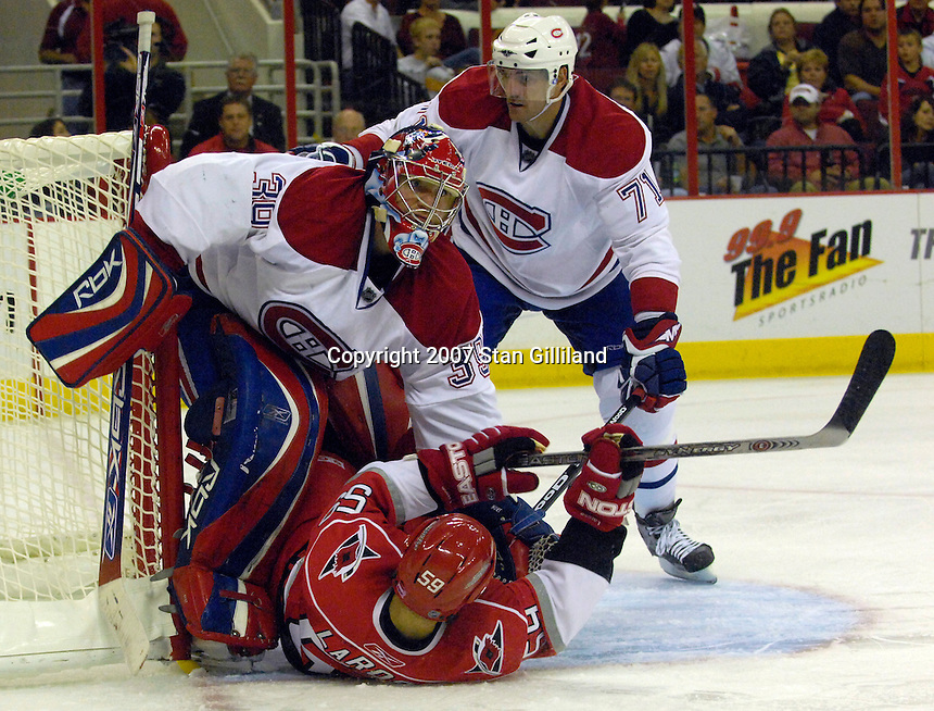 Carolina Hurricanes' Chad LaRose slides into the Montreal Canadiens' goalie Cristobal Huet (39) as teammate Patrice Brisebois (71) watches during their game Friday, Oct. 26, 2007 in Raleigh, NC. The Canadiens won 7-4.