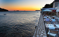Sunset over the sea, restaurant terrace with people eating having dinner. Hotel and restaurant Kompas. Uvala Sumartin bay between Babin Kuk and Lapad peninsulas. Dubrovnik, new city. Dalmatian Coast, Croatia, Europe.