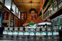 Man working in his tea shop while preparing a customer order, Datong, Shanxi, China.