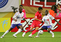 Young Pyo Lee (12) of the Korea Republic is defended by William Gallas (5) and Claude Makelele (6) of France. The Korea Republic and France played to a 1-1 tie in their FIFA World Cup Group G match at the Zentralstadion, Leipzig, Germany, June 18, 2006.