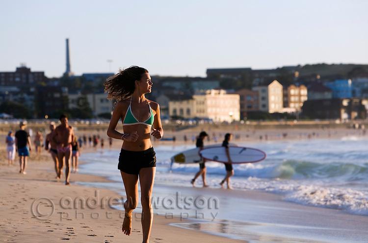 A woman jogging on the beach at Bondi.  Bondi Beach, Sydney, New South Wales, AUSTRALIA.