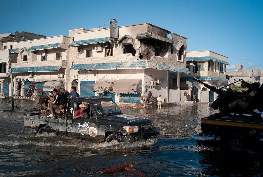 Anti-Gaddafi fighter drive through flooded streets in pickup trucks mounted with anti-aircraft guns in Sirte, Libya.