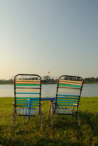 Asia, Vietnam, Hue. Waiting for customers. Chairs at the river Huong (Perfume River). In the distance the flag tower of the citadel.