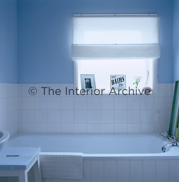 The simple bathroom has a blue and white colour scheme and a wood panelled bath