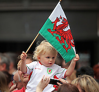 "Pictured: A young Wales fan in St Mary's Street, Cardiff Friday 08 July 2016<br /> Re: Thousands of fans are expected to line the streets to welcome back the Wales national team. An open top bus will parade through Cardiff, from Cardiff Castle to Cardiff City Stadium where the Manic Street Preachers will play to 33,000 people.<br /> The parade comes after Wales lost 2-0 to Portugal in the semi-final on Wednesday, with their historic run hailed as a performance which has ""changed Welsh football forever""."