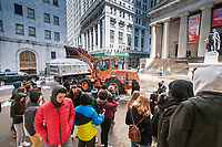 A group of tourists watches as New York Department of Sanitation workers use heave equipment  to remove snow from Wall Street in front of Federal Hall and the New York Stock Exchange after Winter Storm Stella on Thursday, March 16, 2017. (© Richard B. Levine)