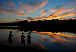 UConn students from Storrs Conn., Gary Tu , Danny Wang and Victor Zheng, stop to admire the sunset set while fishing at Shenipisit Lake, Tuesday evening, August 19, 2014,  in Tolland. (AP / Journal Inquirer, Jim Michaud)
