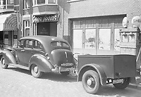 Photo from the NIOD's Huizinga collection. A passenger car with a wood gas generator in a trailer is parked in The Hague