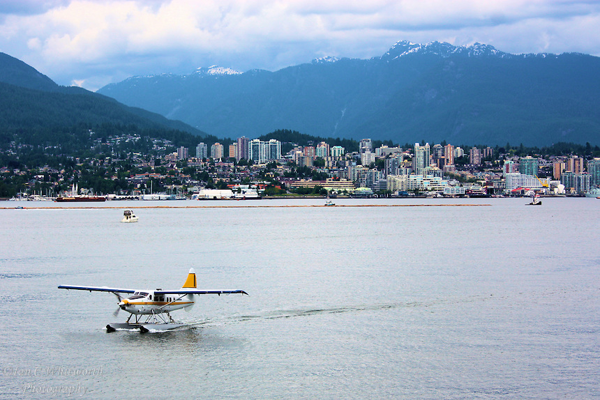 A sea plane taxiing to the water airport with North Vancouver in the background