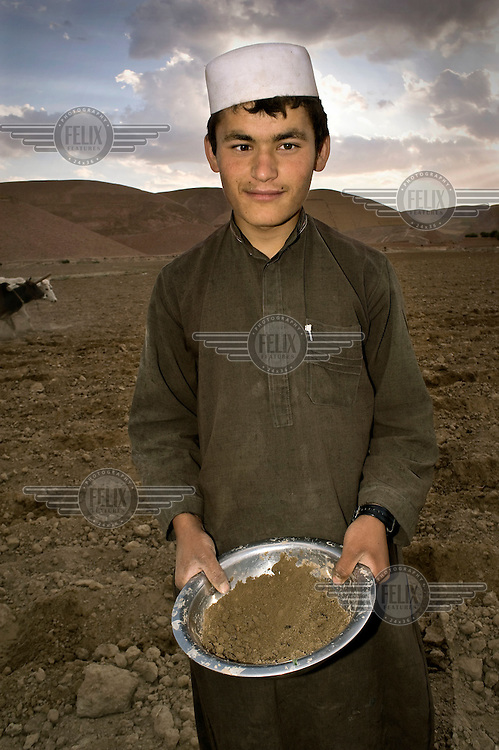 A boy holds a metal bowl containing watermelon seeds.