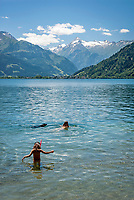 Oesterreich, Salzburger Land, bei Thumersbach: Baden im Zeller See vor den schneebedeckten Gipfeln der Glocknergruppe (Kitzsteinhorn) | Austria, Salzburger Land, near Thumersbach: swimming at Zeller Lake with snow capped summits of Glockner mountain range (Kitzsteinhorn summit) at background