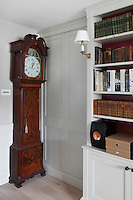 An antique grandfather clock in a corner of the panelled library