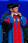 Rick Kash, vice chairman of the global consumer information analytics firm Nielsen, is hooded by Ray Whittington, dean of the Driehaus College of Business,  as he receives his honorary degree Sunday, June 11, 2017, during the DePaul University Driehaus College of Business commencement ceremony at the Allstate Arena in Rosemont, IL. (DePaul University/Jamie Moncrief)
