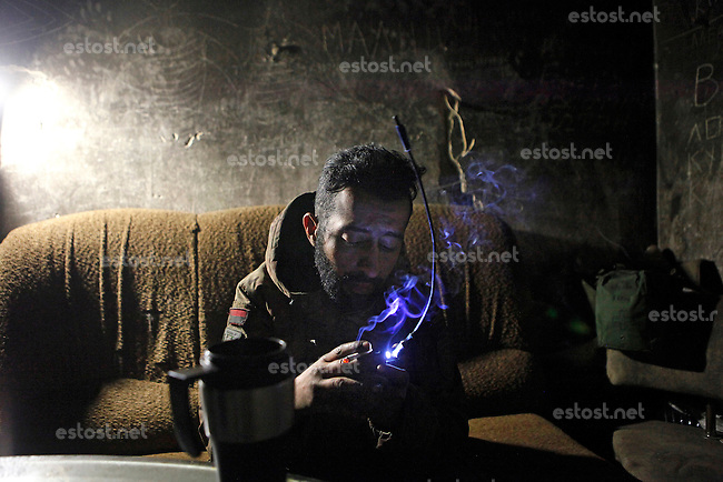 """UKRAINE, 02.2016, Oblast Donetsk. Ukrainian-Russian conflict concerning Eastern Ukraine / Foreign volunteers (""""Task Force Pluto"""") fighting with the far-right militia Pravyi Sektor against the Russian-backed separatists: Ben (Austria) sits in a safe house of the Ukrainian army scanning the radio for public radio reception and smoking a cigarette. © Timo Vogt/EST&OST"""
